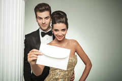 Giovani coppie felici che presentano un invito alle loro nozze immagini stock