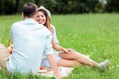 Giovani coppie felici che si divertono in un parco, sedentesi su una coperta di picnic immagini stock libere da diritti