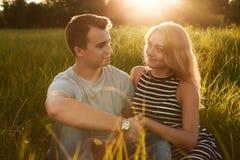 Giovani coppie felici che si siedono insieme sull'erba che tiene le loro mani immagine stock libera da diritti