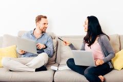 Giovani coppie felici che si siedono su uno strato con il computer portatile immagini stock