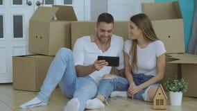 Giovani coppie felici che si siedono sul pavimento facendo uso del computer della compressa per trovare servizio di trasporto per stock footage