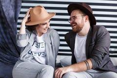 Giovani coppie felici che si siedono sul pavimento nel loro piano isolato su fondo a strisce in studio Fotografia Stock