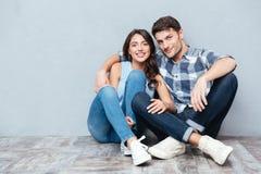 Giovani coppie felici che si siedono sul pavimento sopra bakground grigio Fotografia Stock