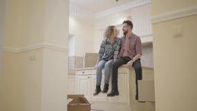 Giovani coppie felici che si siedono sul tavolo da cucina in un nuovo appartamento che discute la disposizione della casa Movimen video d archivio
