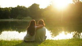 Giovani coppie felici che si siedono sull'erba verde vicino al lago durante il tramonto Punto di vista posteriore della donna e d video d archivio