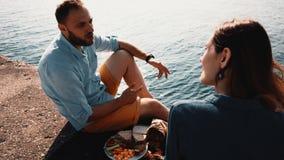 Giovani coppie felici che si siedono sulla riva di un mare e di un cibo Uomo e donna che hanno picnic vicino ad acqua di mattina archivi video