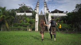 Giovani coppie felici che si tengono per mano e che corrono verso il mandir sviluppato nella giungla, archivi video