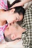 Giovani coppie felici che si trovano sul pavimento e sul baciare Fotografia Stock