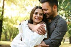 Giovani coppie felici che stanno nell'abbraccio del parco fotografia stock libera da diritti