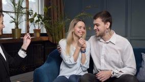 Giovani coppie felici che stringono le mani all'agente immobiliare dopo il riuscito affare stock footage