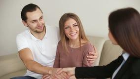 Giovani coppie felici che stringono le mani con il mediatore