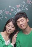 Giovani coppie felici con gli occhi chiusi davanti alla lavagna con i cuori Immagine Stock
