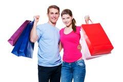 Giovani coppie felici con i sacchetti della spesa Immagini Stock Libere da Diritti