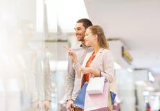Giovani coppie felici con i sacchetti della spesa in centro commerciale Immagini Stock
