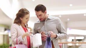 Giovani coppie felici con i sacchetti della spesa in centro commerciale video d archivio
