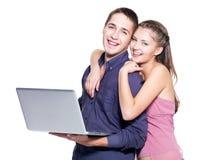 Giovani coppie felici con il computer portatile Fotografia Stock Libera da Diritti