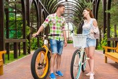 Giovani coppie felici con le bici in arco Immagini Stock Libere da Diritti
