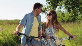 Giovani coppie felici con le biciclette di estate stock footage