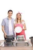Giovani coppie felici con le pile di piatti puliti Fotografia Stock