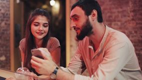 Giovani coppie felici con seduta di conversazione e bevente dello smartphone della bevanda alla barra Amici che per mezzo dello s archivi video