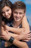 Giovani coppie felici delicatamente abbracciare & cielo blu Fotografia Stock Libera da Diritti