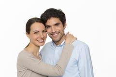 Giovani coppie felici dell'amante che stanno sul fondo bianco, isolato Immagine Stock