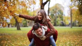 Giovani coppie felici divertendosi nel parco di autunno archivi video