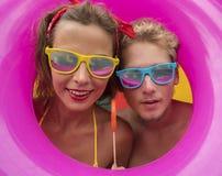 Giovani coppie felici divertenti della spiaggia che sorridono in mezzo all'anello gonfiabile rosa Immagini Stock