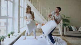 Giovani coppie felici ed amorose che hanno lotta di cuscino a letto a casa fotografia stock