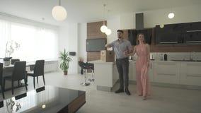 Giovani coppie felici emozionanti che guardano intorno alla progettazione moderna d'avanguardia della cucina interna che si muove