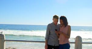 Giovani coppie felici facendo uso del telefono cellulare vicino alle inferriate 4k video d archivio