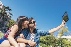 Giovani coppie felici facendo uso della compressa nel parco Fotografia Stock Libera da Diritti