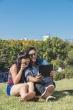 Giovani coppie felici facendo uso della compressa nel parco Fotografia Stock