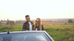 Giovani coppie felici facendo uso della mappa durante il viaggio sul cabriolet stock footage