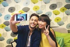 Giovani coppie felici facendo uso dello smartphone nella barra Fotografia Stock Libera da Diritti