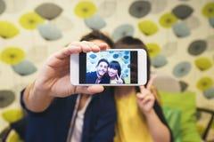 Giovani coppie felici facendo uso dello smartphone nella barra Immagine Stock Libera da Diritti
