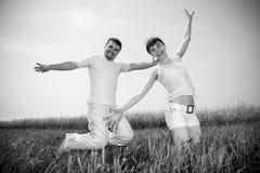 Giovani coppie felici - la squadra sta saltando Fotografia Stock