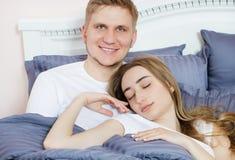 Giovani coppie felici a letto, famiglia in camera da letto dopo sonno, fine settimana fotografia stock libera da diritti