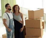 Giovani coppie felici Muovendosi, alloggi nuovi d'acquisto Fotografie Stock Libere da Diritti