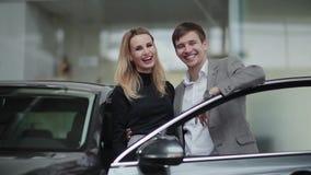 Giovani coppie felici nel concessionario auto stock footage