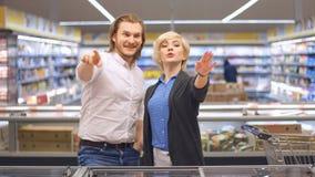 Giovani coppie felici nel supermercato che sceglie i prodotti per una celebrazione di famiglia archivi video