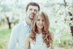 Giovani coppie felici nell'amore all'aperto uomo e donna amorosi su una passeggiata al parco di fioritura della molla Fotografia Stock Libera da Diritti