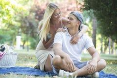 Giovani coppie felici nell'amore che si rilassa e che ha picnic in parco immagine stock