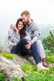 Giovani coppie felici nell'amore che si siede su una montagna, abbracciare e su un lo Fotografia Stock