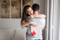 Giovani coppie felici nell'amore sorprendente con i regali immagini stock libere da diritti