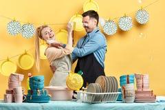 Giovani coppie felici prendere piacere dai piatti del wahisng immagine stock