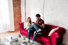 Giovani coppie felici rilassate a casa con un animale domestico del coniglietto fotografia stock libera da diritti