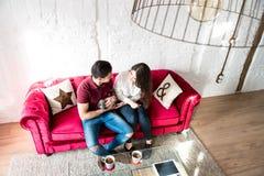 Giovani coppie felici rilassate a casa con un animale domestico del coniglietto immagini stock