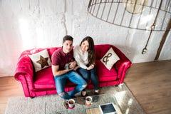 Giovani coppie felici rilassate a casa con un animale domestico del coniglietto fotografia stock