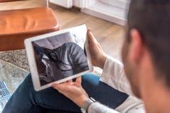 Giovani coppie felici rilassate a casa con un tabet fotografia stock